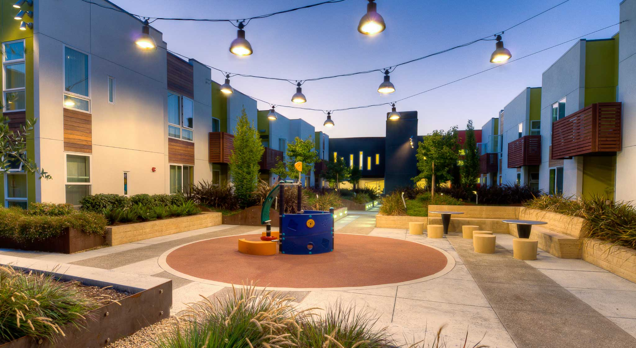 Evening view of a courtyard at Tassafaronga Village with playground between multifamily buildings
