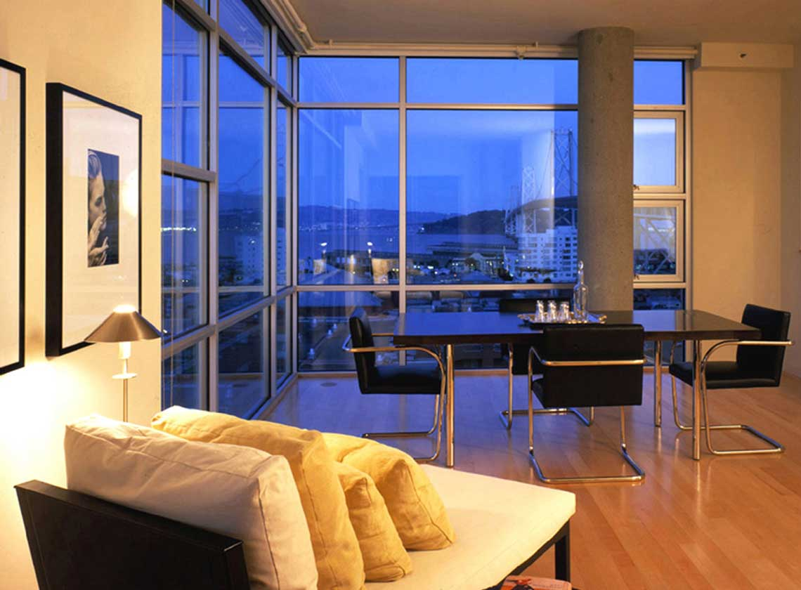 Interior evening view of furnished dining area with views of the Bay Bridge through floor to ceiling windows