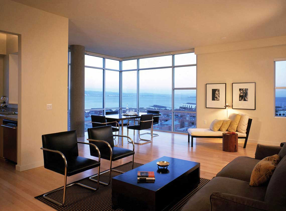 Interior evening view of furnished modern unit interior with views of the bay through floor to ceiling windows