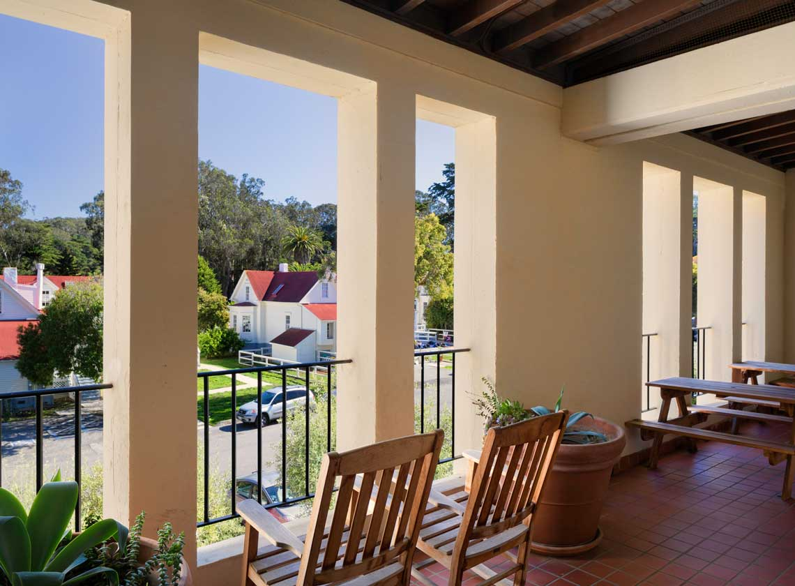Daytime exterior view of Mesa Street from 2nd floor veranda with wooden chairs overlooking other Presidio structures