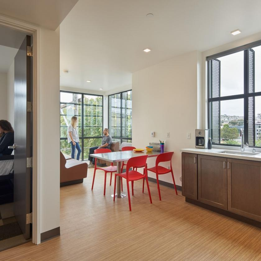 Interior view of shared community kitchenette, dining, and seating area with large windows