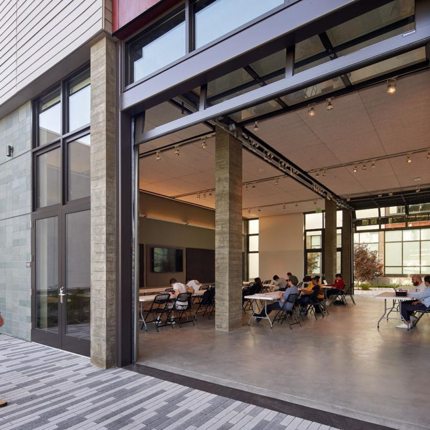 Daytime view looking into a large open modern interior learning space through a retractable garage door