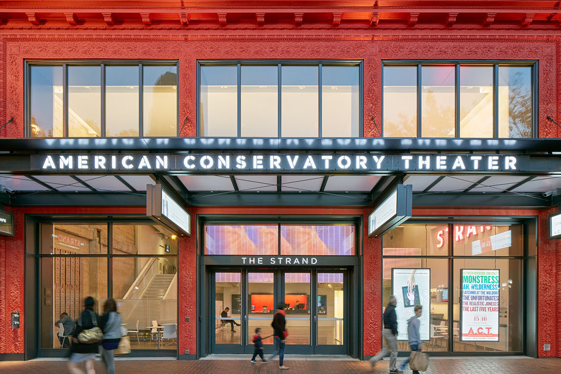 Close view of entry with illuminated American Conservatory Theater sign on overhang; lobby is visible through large windows