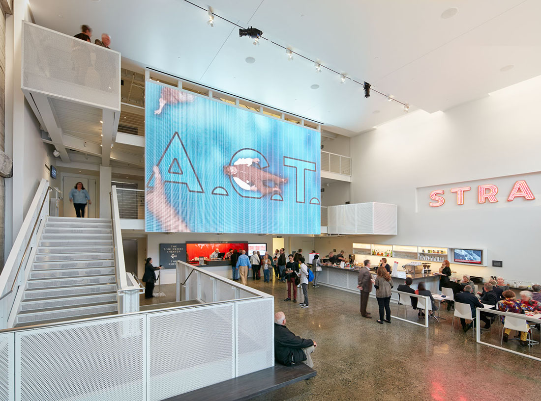 Interior view of lobby with guests mingling and a large digital display spanning two floors.