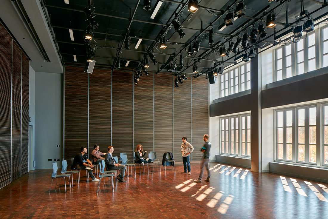 Rehearsal room with wood floors and daylight through large windows; people seated in loosely arranged chairs.