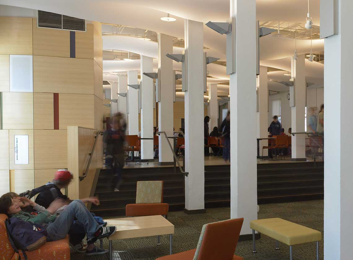 Students seated and walking in an interior hallway and lounge with colorful wall accents and furniture
