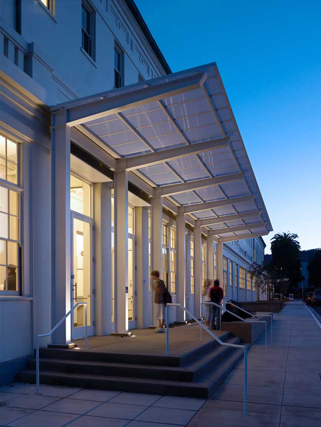Exterior evening view of building with modern renovated entry overhang; interior lighting visible through large windows