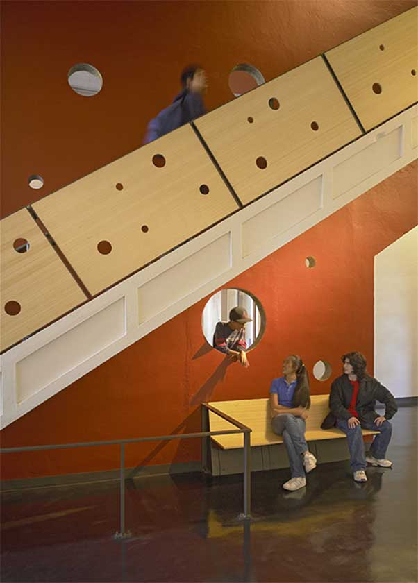 Young people chat near playful interior staircase with holes of various sizes cut in the handrail siding and walls between rooms