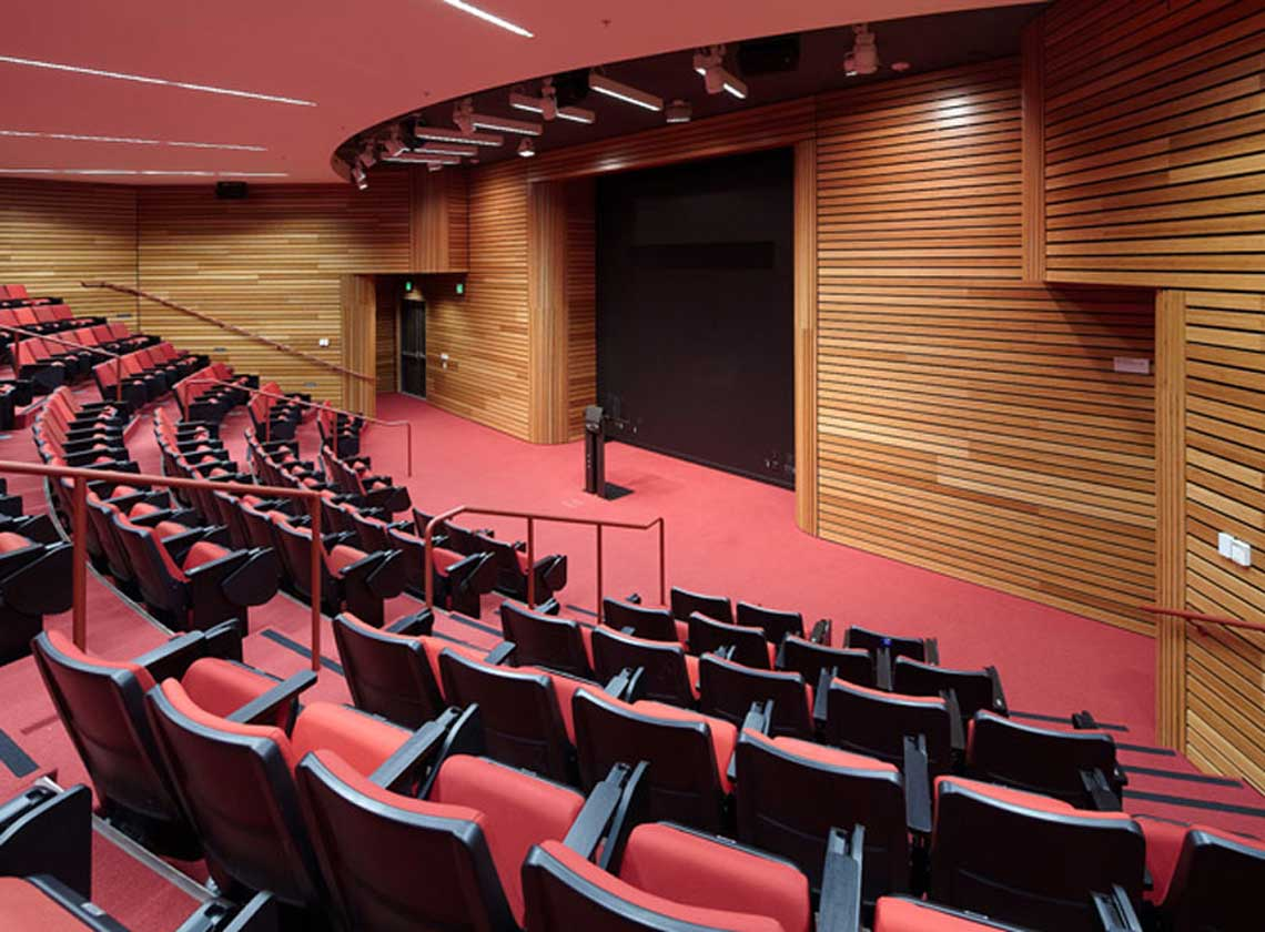 Interior view of theater / meeting space with red seats and carpet with wood panel walls