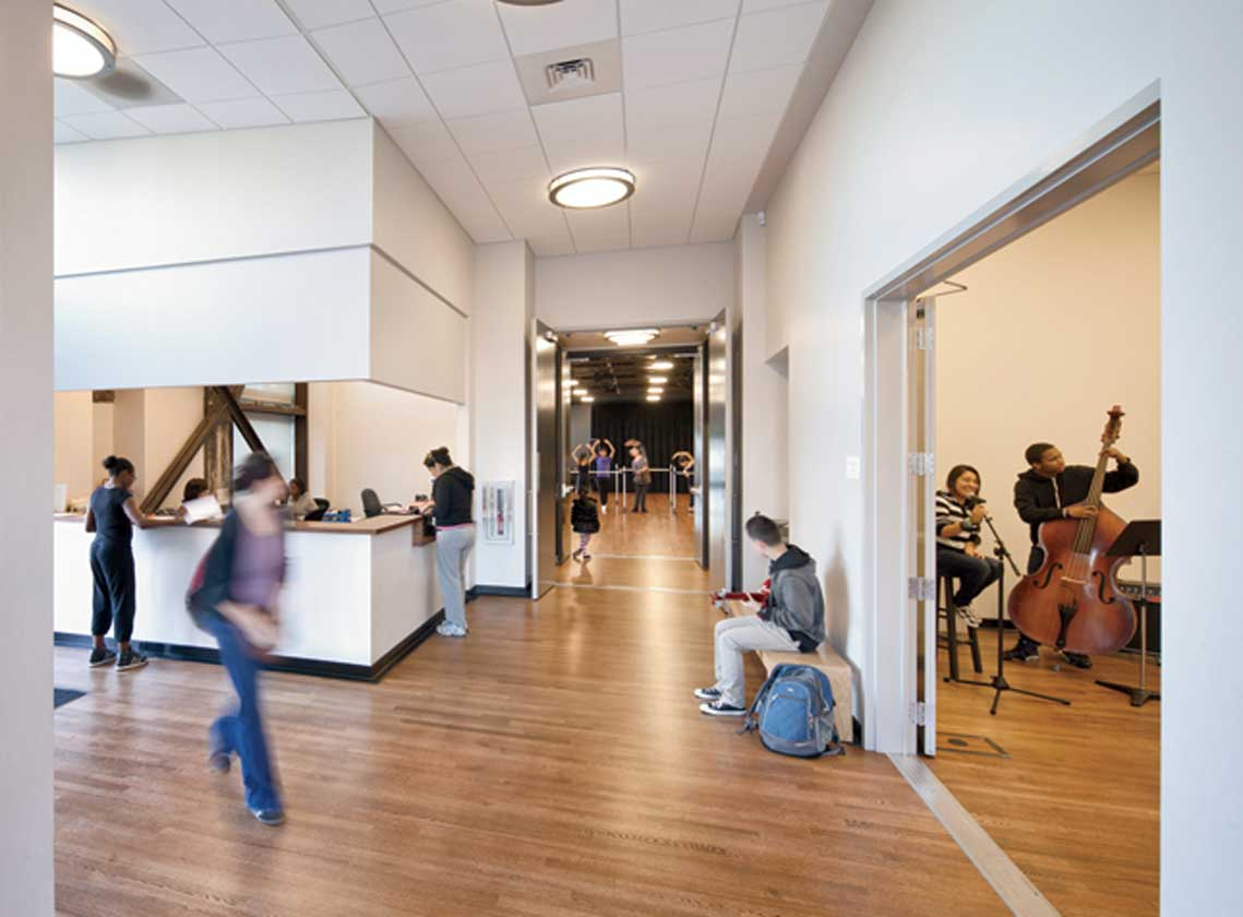Interior lobby, hallway and reception desk with views into rehearsal spaces