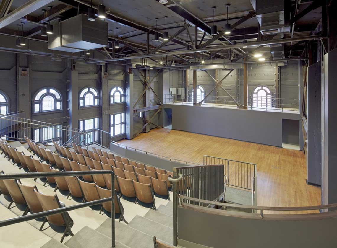 Performance space as viewed from top row of balcony with large arched windows and exposed concrete structure