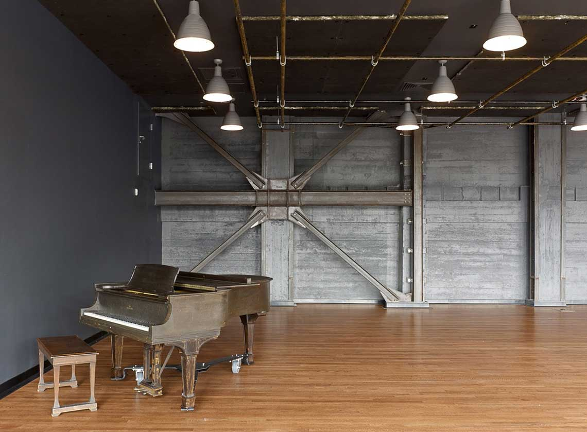 Rehearsal space with hardwood floors and exposed industrial wall and ceiling details; a piano in the foreground
