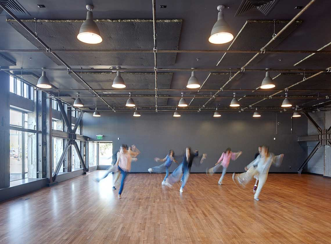 Young people in motion practicing a dance routine in a brightly-lit rehearsal space