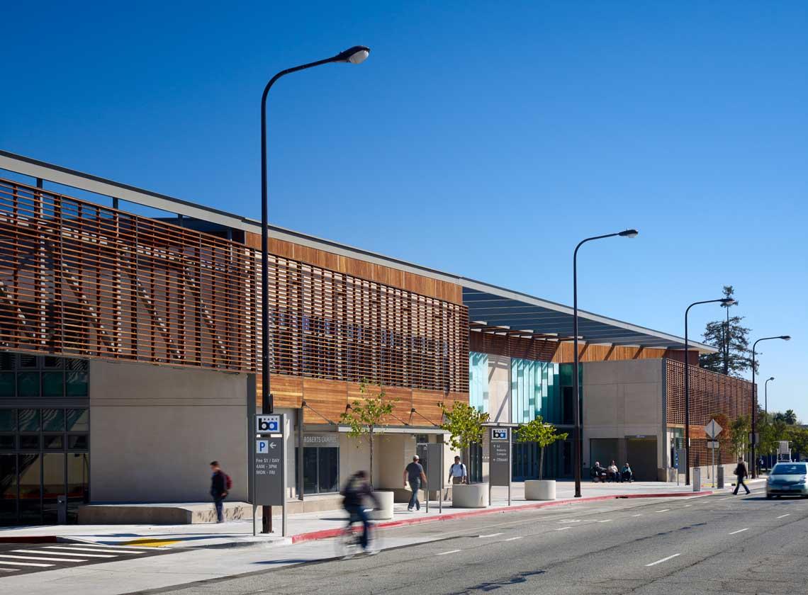 Building façade with modern wooden slat details along Adeline Street; BART entrance and parking signs along the sidewalk.