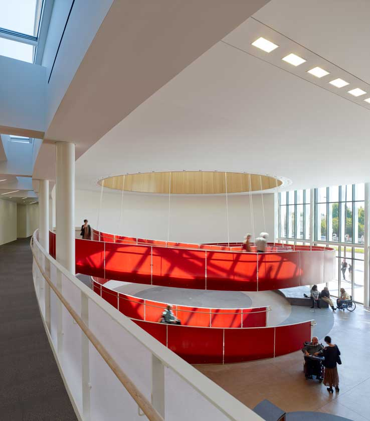 Interior view of lobby with bold red accessible spiral ramp as seen from a second-floor corridor