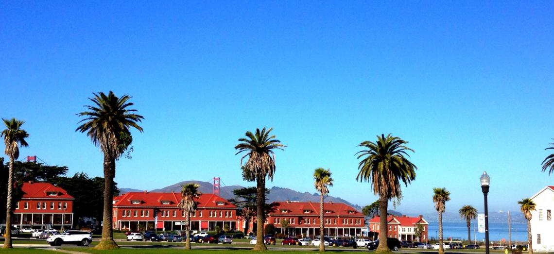 View of lawn and main post in the Presidio of San Francisco with brick buildings nad Golden Gate Bridge in background.