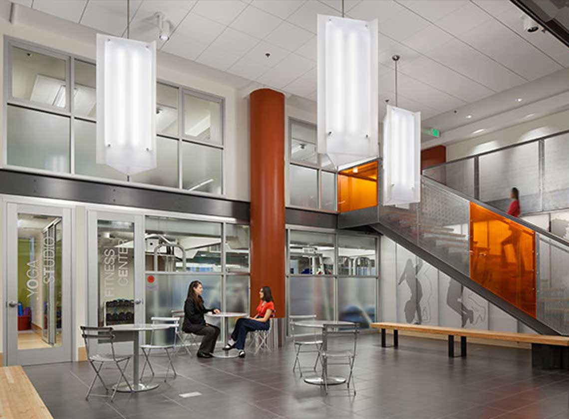 Interior communal space with cafe-style tables, benches, and doorways to a yoga studio and fitness center