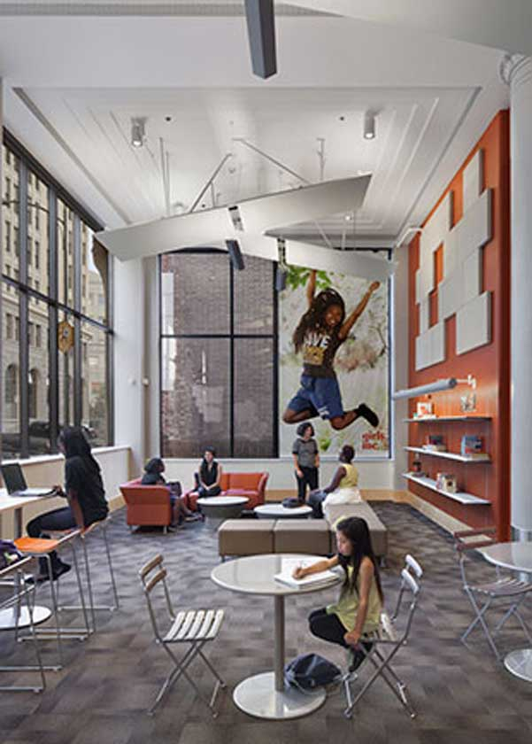 Interior view of lounge with tables and chairs. A large mural of a girl jumping is printed on the far wall