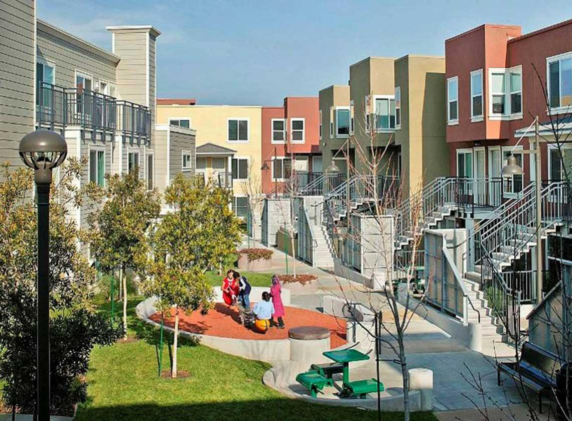 Colorful exterior walls of multifamily units facing a landscaped courtyard with picnic table and play area