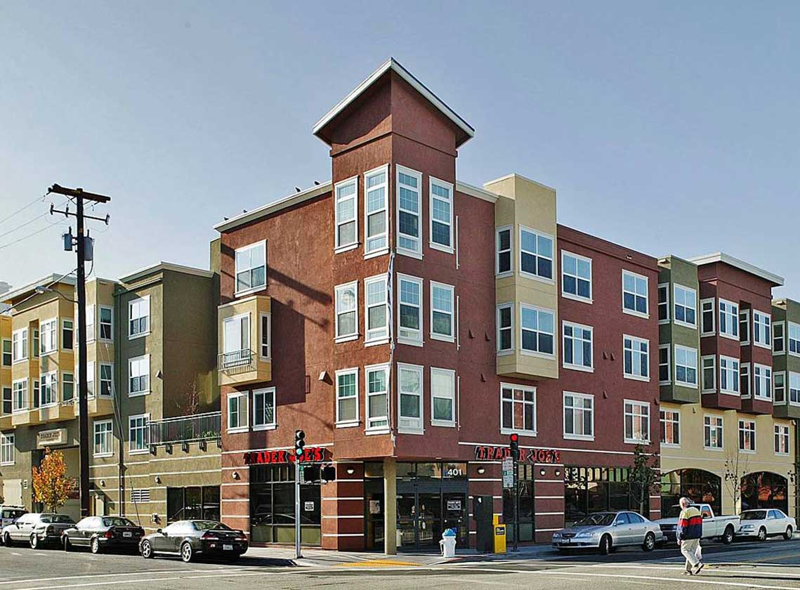 Exterior daytime corner view of multifamily units above Trader Joe's ground floor retail
