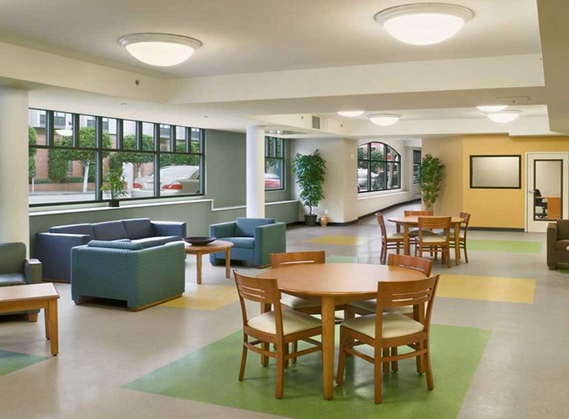 Interior community space with tables and arm chairs. Colorful green and yellow shapes accent the tile floor