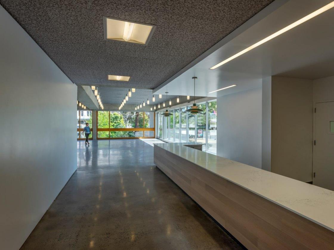 Museum interior hallway leading to floor to ceiling windows.
