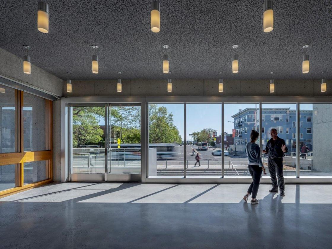 Museum interior with people looking out floor to ceiling windows to terrace and city..