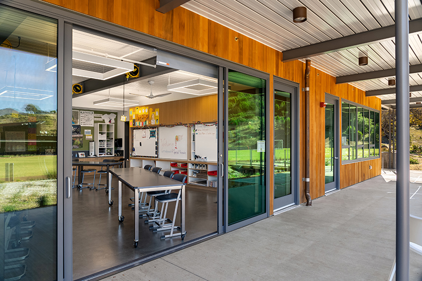 Exterior view looking into classroom through large sliding glass walls, connecting classroom to nature