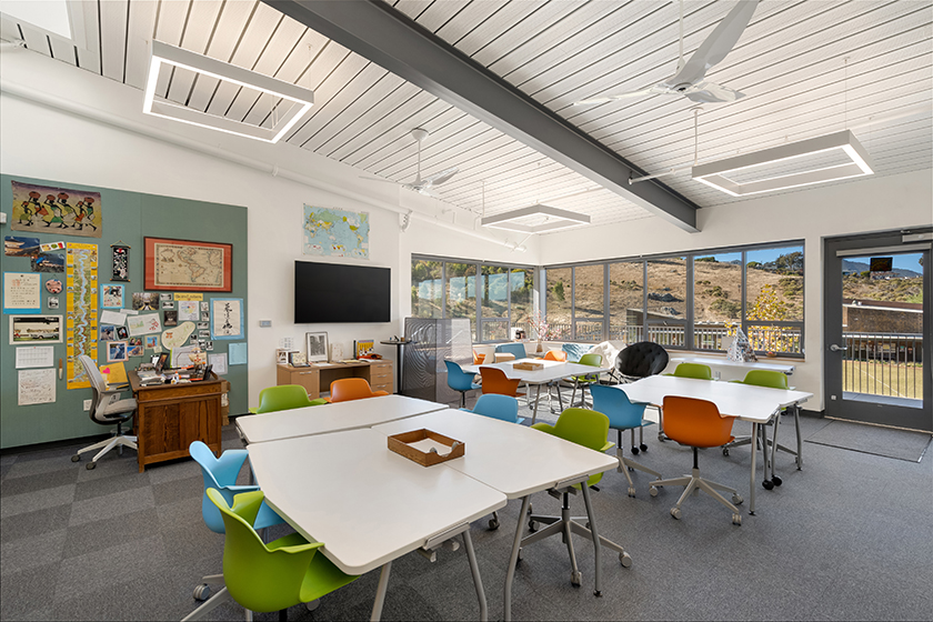 Interior view of bright modern classroom with rearrangeable tables and rolling chairs in bright accent colors