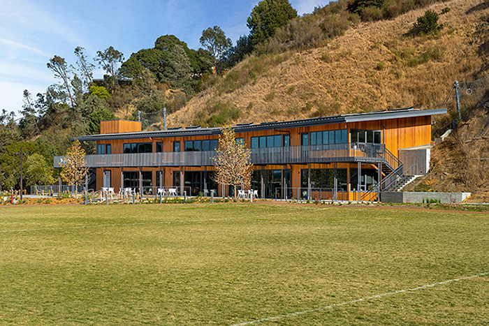 Exterior daytime view of school building nestled into a hill, as seen from across a large grass field