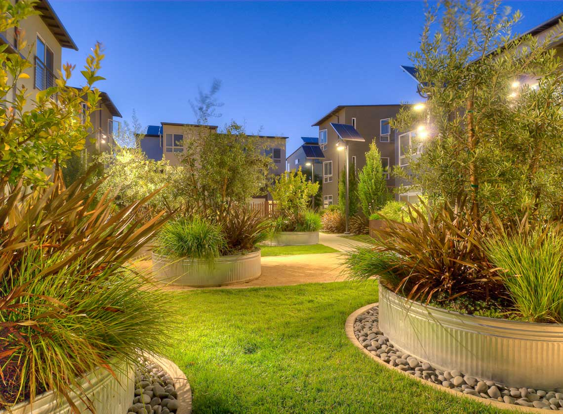 Detail of exterior courtyard landscaping with large round metal planters and lawn at dusk