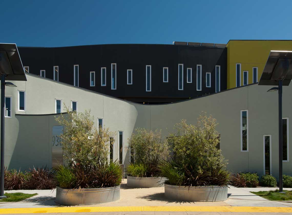 Exterior view of curving architectural walls with slim windows at staggered heights, large planters in the foreground
