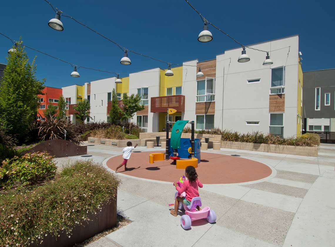 Exterior daytime view of landscaped courtyard with children in a play area under strings of hanging down lights