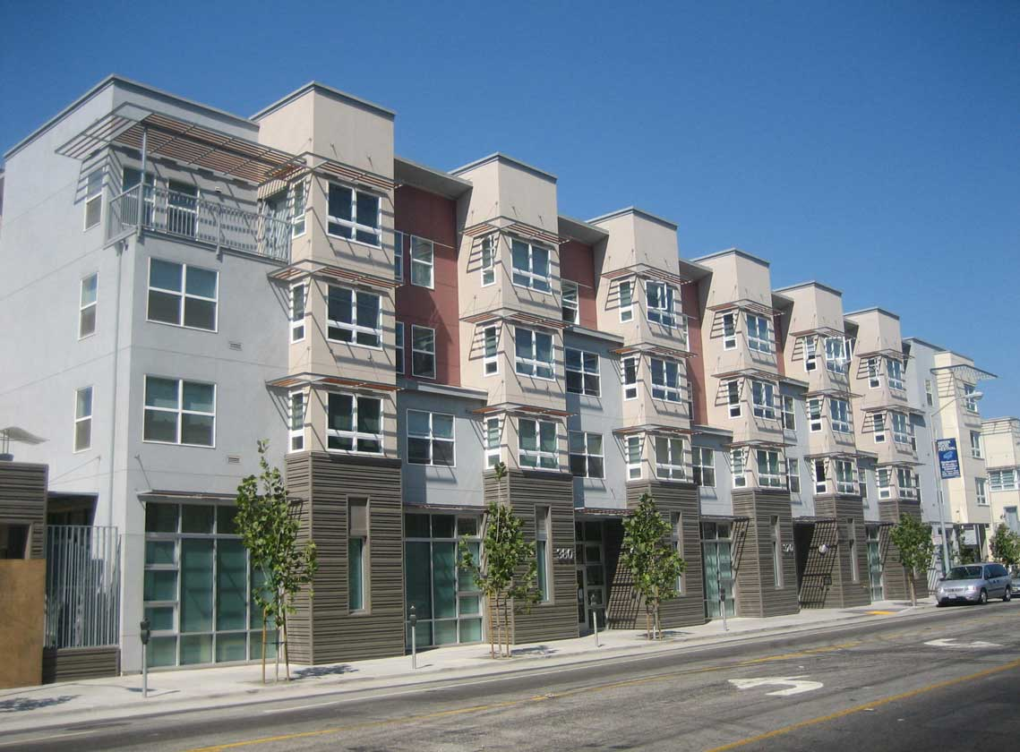 Exterior daytime view of multifamily units with architectural details and a variety of wall colors