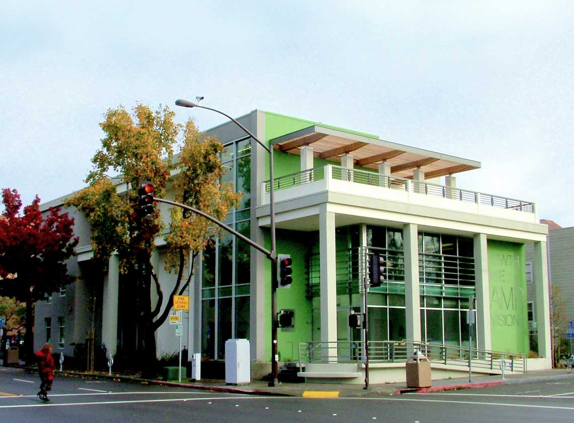 Exterior daytime corner view of three-floor building with bright green accents, bold graphic signage, and columns