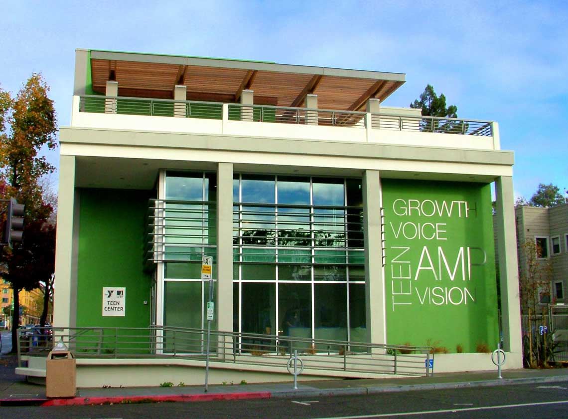 Front view of building entry from street level with bright green façade walls and large graphic words