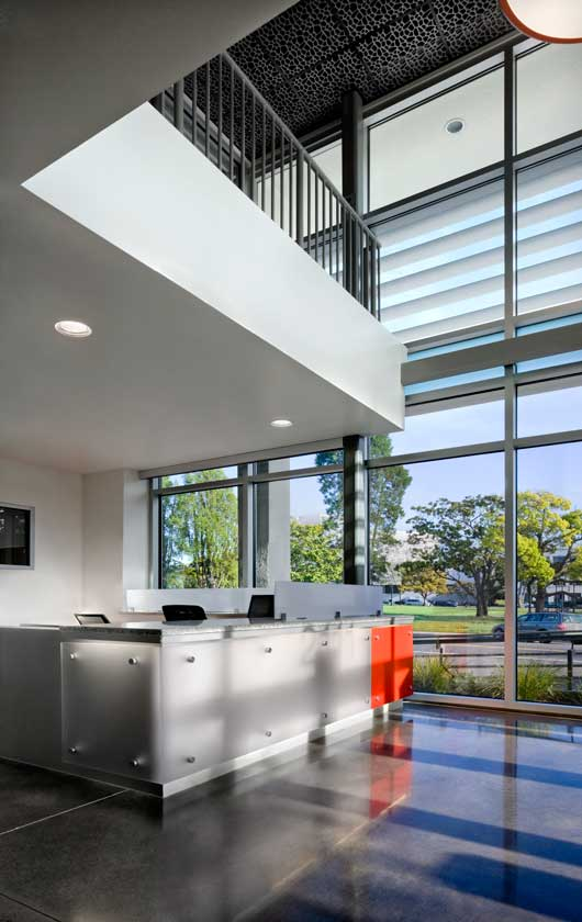 Interior view of lobby reception with view to street through large double-height floor to ceiling windows