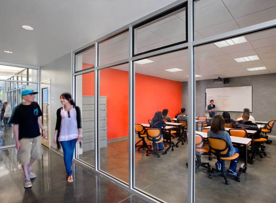 Interior view of hallway and classroom through glass walls; students at tables attending a lecture