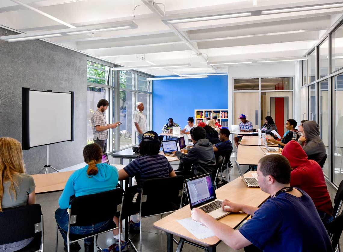 Students seated at tables with laptops in a bright classroom space with window and a blue accent wall