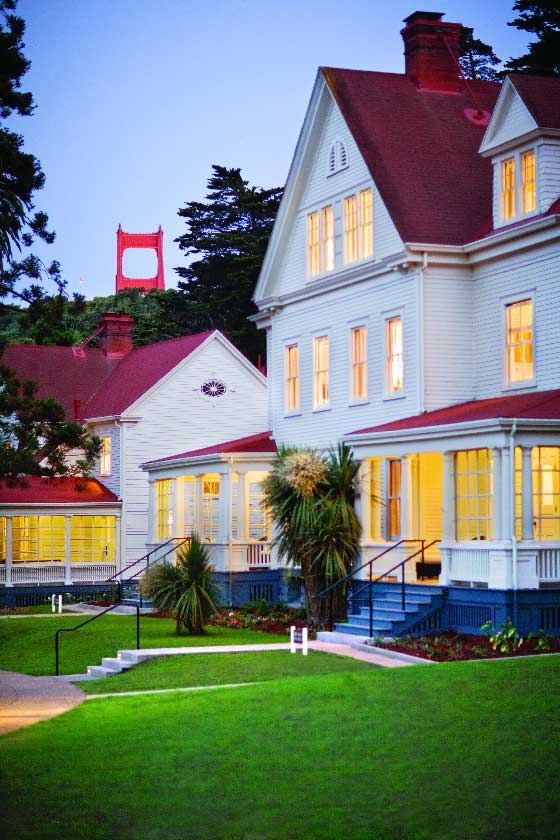 Evening view of a lodge building illuminated from inside with top of Golden Gate Bridge in the distance.