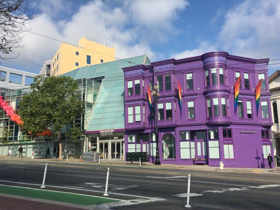 Exterior daytime view along Market street, with historic structure painted purple connected to modern glass addition